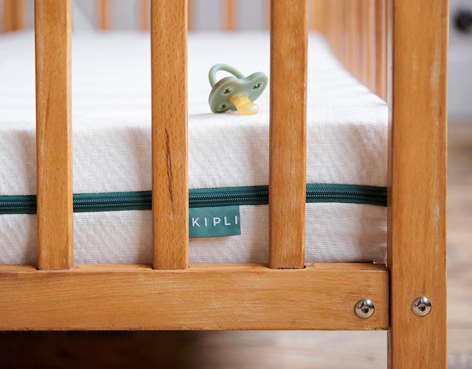 Matelas bébé dans lit à barreaux avec étiquette Kipli