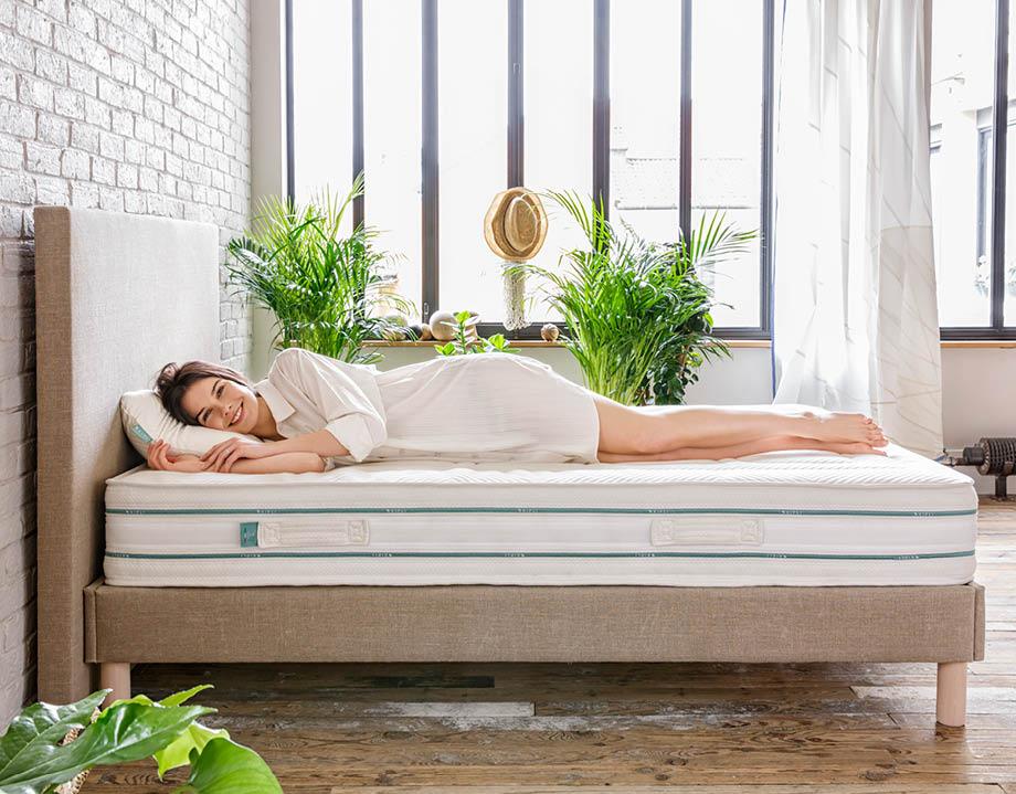 Frau liegt seitlich auf einer Kipli Matratze in einem natürlichen Schlafzimmer mit Pflanzen