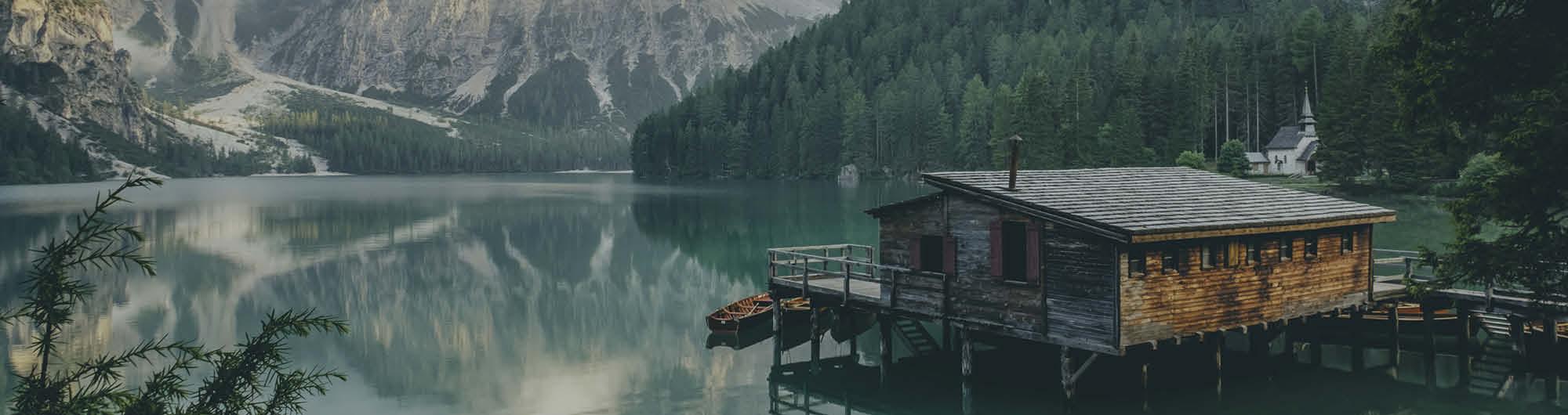 Haus am See in der Natur mit Bergen im Hintergrund