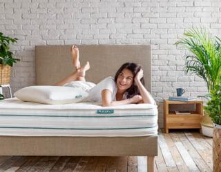 Modelo acostada sobre el colchón de látex natural y la cama tapizada Kipli