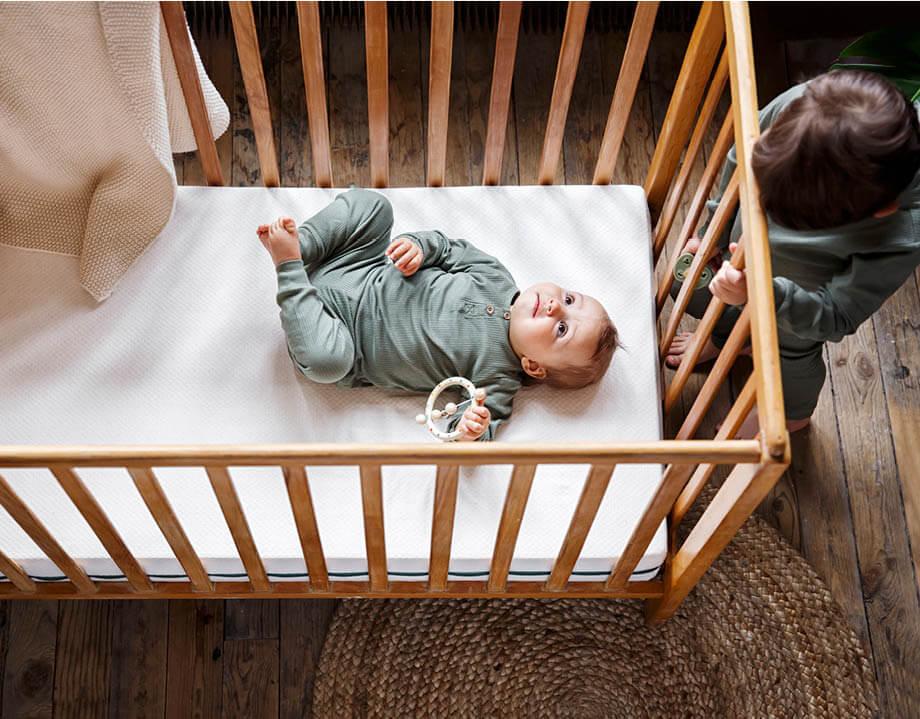 Matelas bébé bio Kipli avec un bébé allongé et enfant qui le regarde