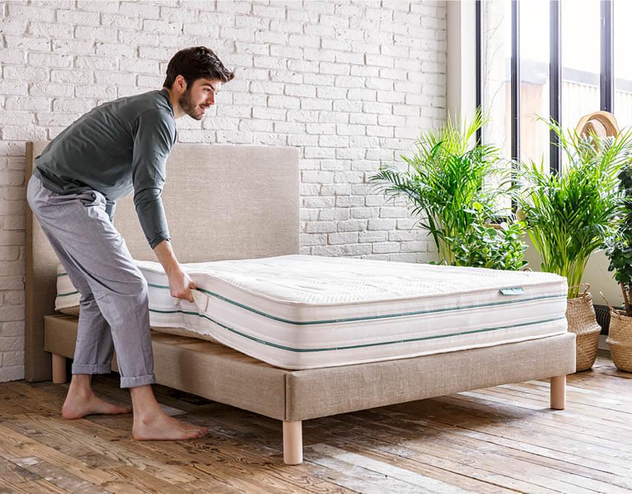 Homme en train de poser le matelas latex naturel sur le sommier tapissier