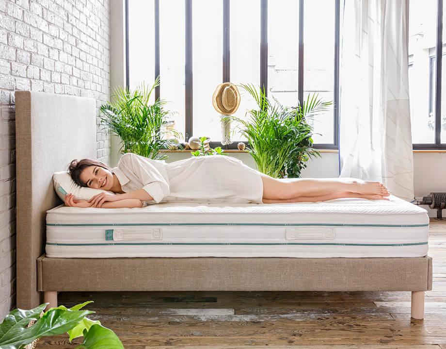 Mujer acostada de lado en la cama tapizada Kipli