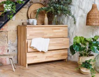 Commode bois massif avec linge de lit et plantes autour