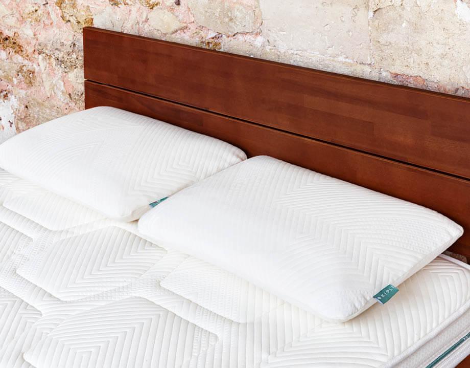 Deux oreillers latex naturel sur lit bois foncé